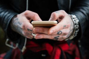 Tattooed hands with mobile