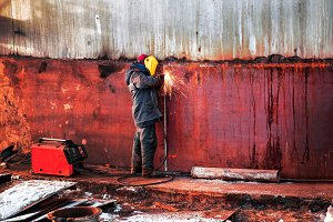 Worker welds the steel wall