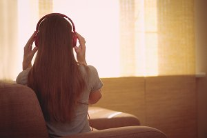 Happy woman with pink headphones listening to music. Young woman sit backwards at home on a couch and enjoy the music with headphones near sunny window