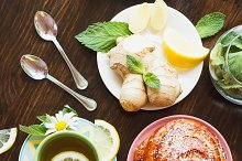 Cup of herbal tea with lemon and mint leaves, ginger root and baked good
