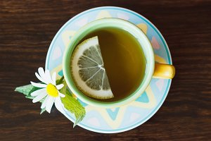 Cup of herbal tea with camomile and mint leaves on the wooden background