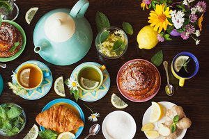 Cups of herbal tea with lemon and mint leaves, ginger root and croissant