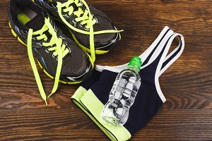 Green sneakers, bottle and sports bra