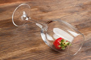 Wineglass with red ripe strawberry inside