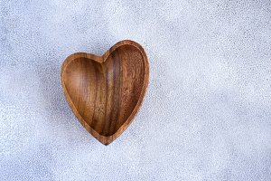 Wooden bowl in the shape of heart on a concrete background