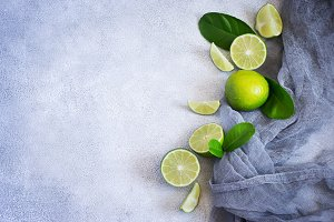 Concrete background with juicy limes. Top view with copy space