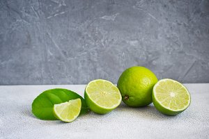 Limes are whole and halves on a gray background, copy space