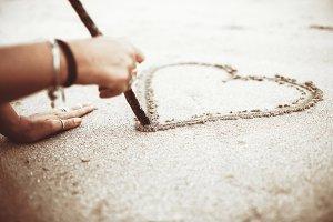 Girl draws heart on the sand