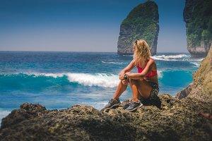 Girl sitting on the Rock and watching Huge Waves hitting Tembeling Coastline at Nusa Penida Island, Bali Indonesia