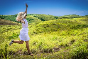 A girl in white dress happy jumping on green grass Hill, Teletubbies Hills, Nusa Penida, Bali, Indonesia
