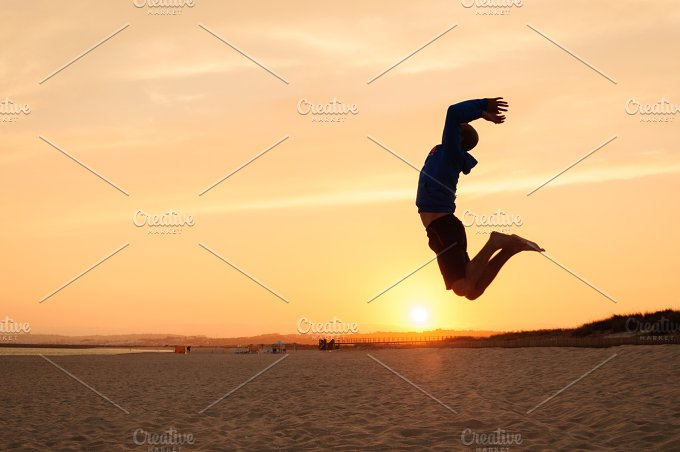 Man silhouette. Jumping at sunset - People
