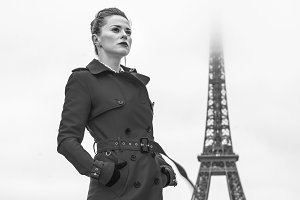young woman standing against Eiffel tower in Paris, France