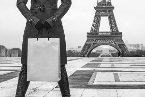 woman against Eiffel tower with shopping bag looking aside