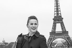 woman in front of Eiffel tower with shopping bag looking aside