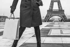 woman in Paris, France with shopping bag looking into distance