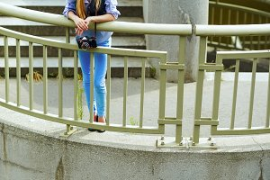 Hipster girl standing on stairs in city