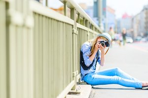 Hipster girl making photo with retro camera while sitting on city street