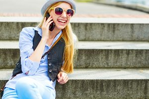 Happy hipster girl talking cell phone while sitting on stairs