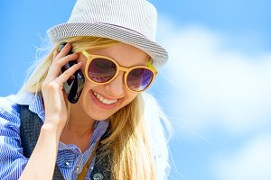 Smiling hipster girl talking mobile phone against sky