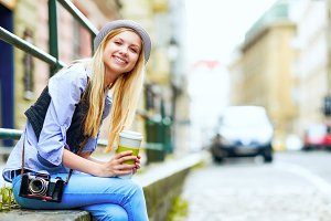 Happy young hipster sitting in the city with cup of hot beverage