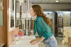 woman looking mirror at faucet store