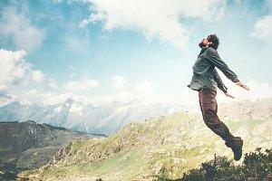 Happy Man jumping at mountains