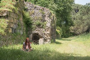 Portrait of a red hair woman in green grass in pompeii, Italy - hot summer midday