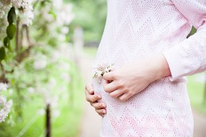 young pregnant woman holding flower