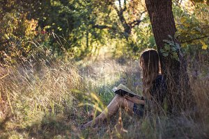 Girl reading book in summer forest