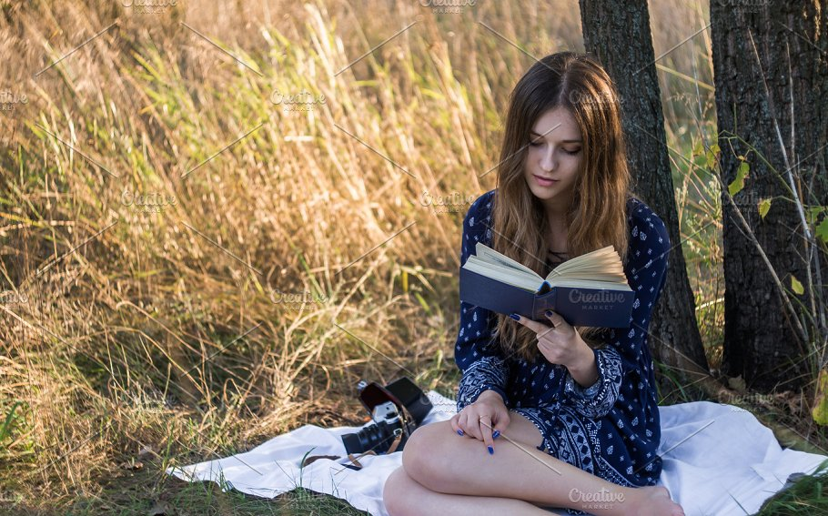 girl reading a book under a tree people images creative market