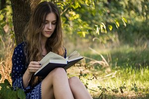 Girl reading a book in summer forest