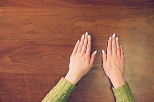 Female hands on wooden background