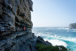 Rough cliff and ocean view with red life buoy