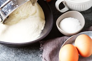 Ingredients for pancakes, flour, milk, eggs. Traditional for the Russian pancake week. Dark background.