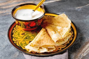 Stack of pancakes on a plate with sour cream. Traditional for the Russian pancake week. Dark background.