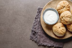 Traditional Russian meat pie, (belyashi) with sour cream. Dark background.