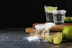 Tequila silver with lime and sea salt. Dark background. Selective focus