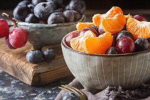 Plate with fruit salad of mandarin, grape, blueberry. Delicious and hearty breakfast options. Dark background.