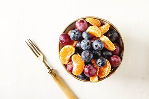 Plate with fruit salad of mandarin, grape, blueberry. Delicious and hearty breakfast options. Light background.