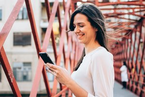 Smiling woman with phone and coffee