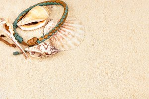 Sea shells and coloured wristbandon on sandy beach