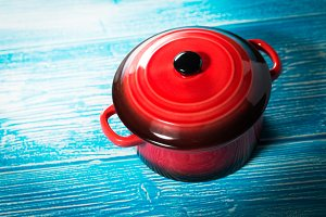 Red pot on blue wooden desk