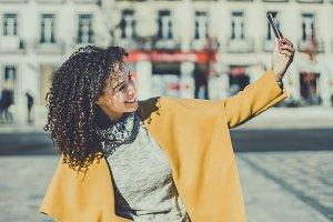 Curly brunette making selfie