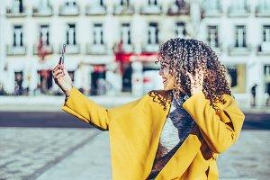 Curly brunette is making selfie