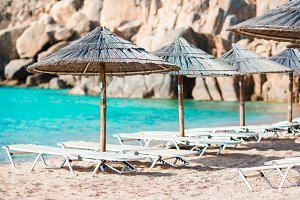 Beach wooden chairs and umbrellas for vacations on beach in Greece