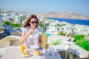 Young tourist girl having breakfast at outdoor cafe with amazing view of old greek town