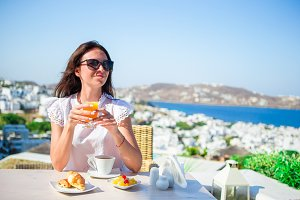 Tourist woman having breakfast with coffee at outdoor cafe with amazing view on Mykonos town.