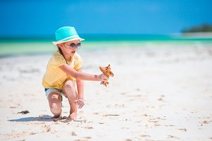 Happy child girl playing with toy airplane on the beach. Kids dream of becoming a pilot