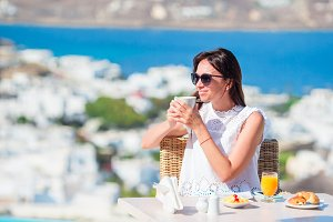 Girl having breakfast at outdoor cafe with amazing view. Woman enjoy her hot coffee early in the morning