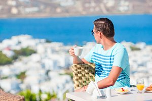 Young guy on breakfast at outdoor cafe with amazing view on Mykonos town.